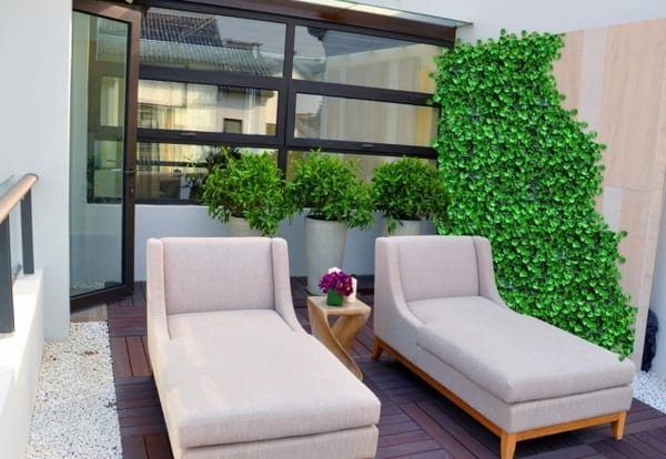 Terrasse mit Holzfliesen und Kies- grüne Wand auf die Terrasse