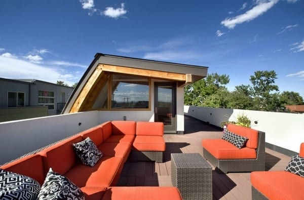 Dachterrasse gestalten mit weißem Massivgeländer und Rattanmöbeln mit roten Polsterkissen
