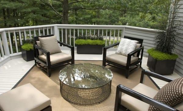weiße Holzterrasse mit Teppich in Taupe Farbe mit schwarzen Terrassenmöbeln und Rundtisch