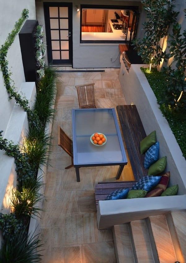 kleine terrasse mit Natursteinplatten und eckbank aus Holz- Esstisch mit Glasplatte und Metallfüßen