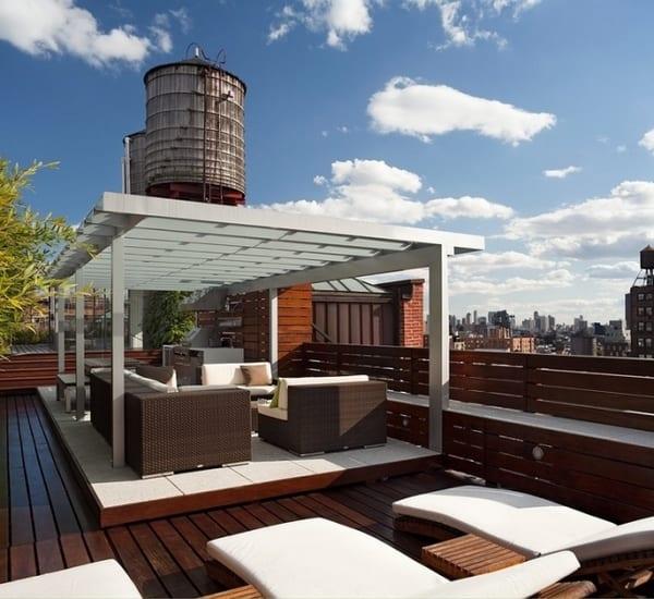 Moderne Terrasse mit holzboden und Holzgeländer mit Sitzfläche- weiße Gartenlaube mit Rattanmöbeln