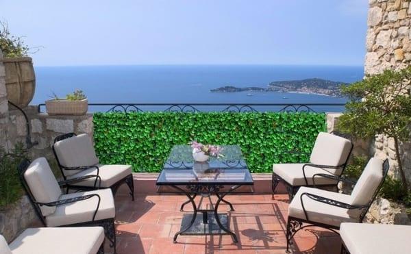 schwarze Terrassenmöbel aus Stahl mit weißen Polsterkissen und Pflanzgeländer