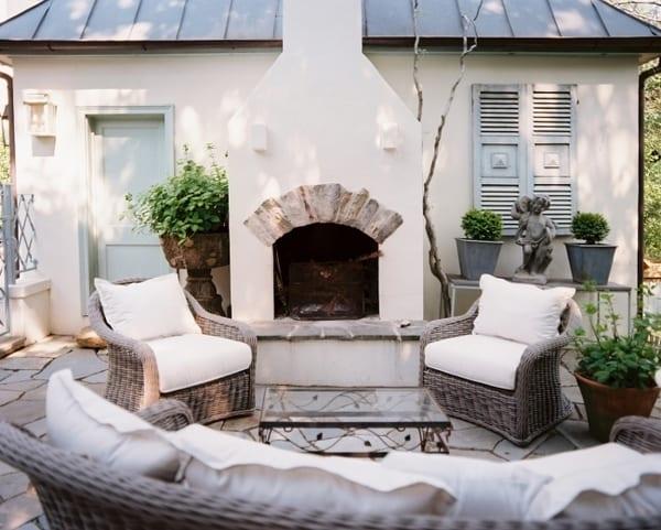 Terrasse mit Natursteinplatten und Rattansesseln mit weißen Kissen
