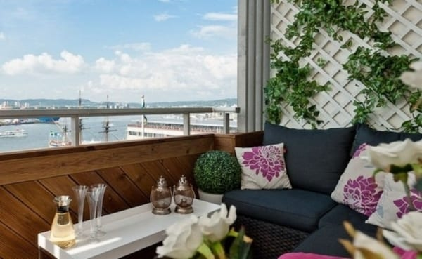 Terrasse mit weißer Wand aus  Holzzaun für Bepflanzung- Rattanecksofa mit dunkelbaluen Sofakissen und weißen Kissen mit Blumenmotiv in violett