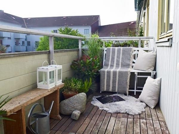 kleine terrasse einrichten mit Holzbank und weißem Metallstuhl mit grauer Decke- weiße Kissen und Laternen
