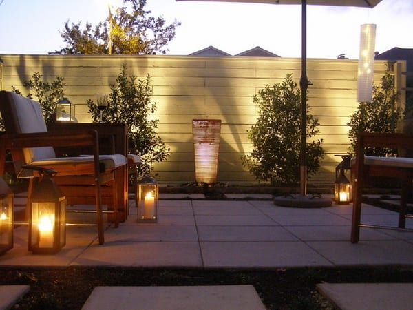 terrasse mit Natursteinplatten und Holzstühlen- weiße Gartenmauer aus Holz