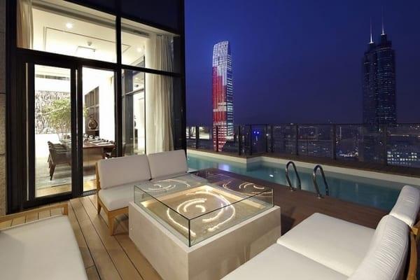 moderne terrassengestaltug mit holzboden und Holzmöbeln mit Weißen Polsterkissen- moderner couchtisch in weiß mit Glasvitrine