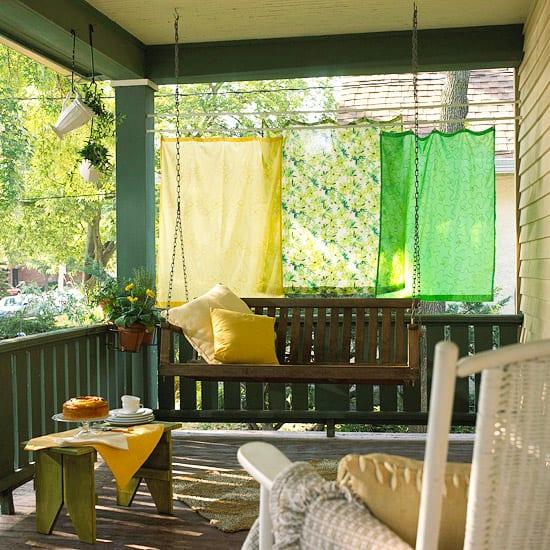 überdachte terrasse mit grünem Holzgeländer und holzschaukel- gardinen grün und gelb