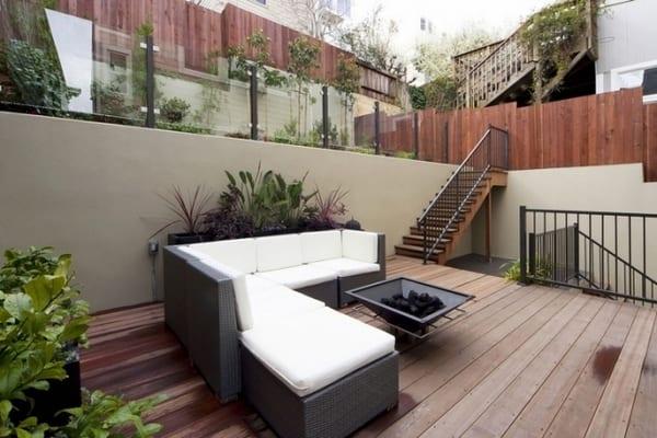 Terrasse mit Holzboden und Holztreppe- Ecksofa mit weißen Polsterkissen