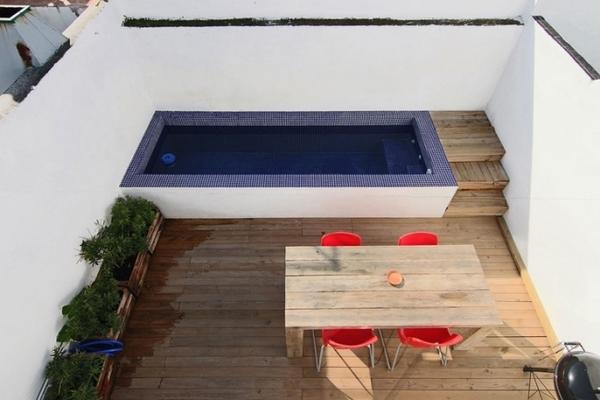 moderne Dachterrasse mit Holzboden und Holzpflanzentöpfen- Holztisch mit roten Stühlen- terrasse mit weißen wänden