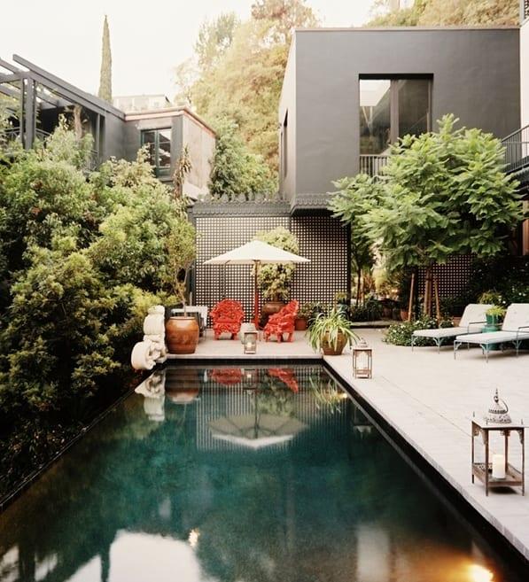 Terrassengestaltung mit Pool und metalllaternen-Terrasse mit intensiver Begrünung-moderner Gartenzaun- haus mit grauen fassaden