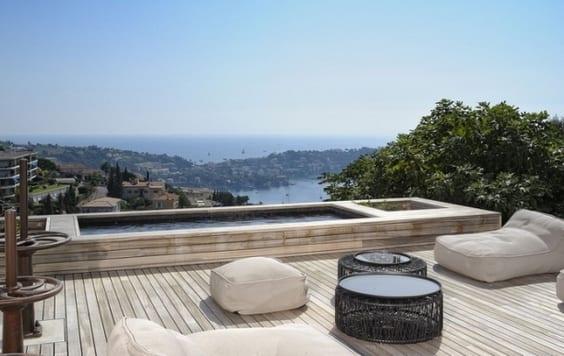 moderne terrassegestaltung aus holz mit tauchbecken und weißen Sitzkissen und schwarzen Rundcouchtischen
