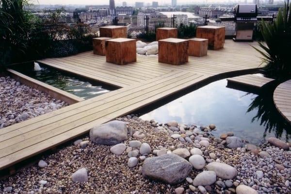 moderne Terrassengestaltung mit Holzboden und wassergarten- moderne Terrassenmöbel aus Holz und offene außenkamin