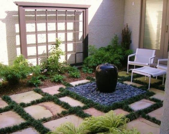 terrasse mit natursteinplatten und kleinen springbrunnen aus schwarzem naturstein