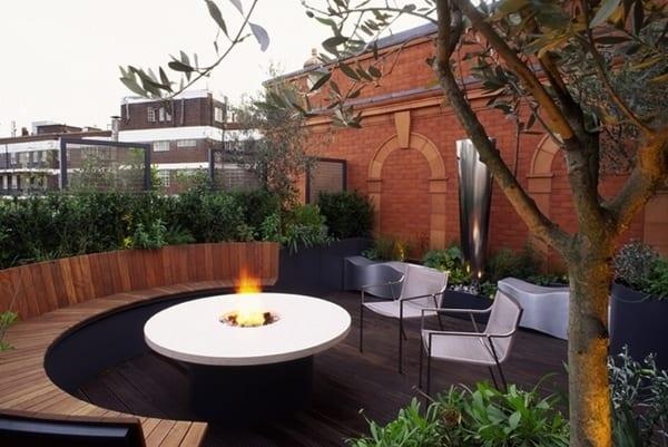 moderne terrasse mit Rundkamin und runder Sitzfläche aus Holz