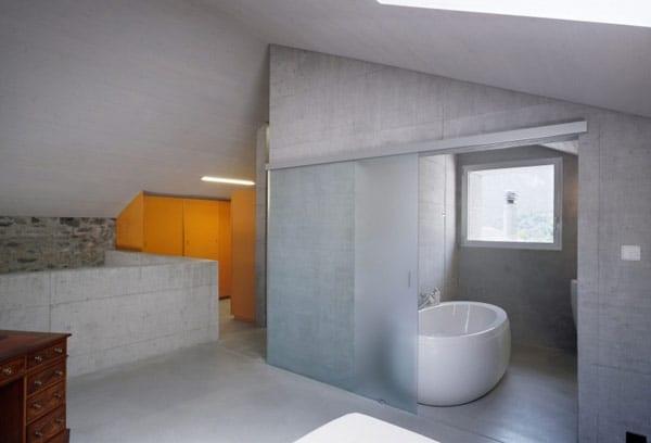 badezimmer aus beton mit weißer freistehende badewanne und großer Schiebetür aus glas