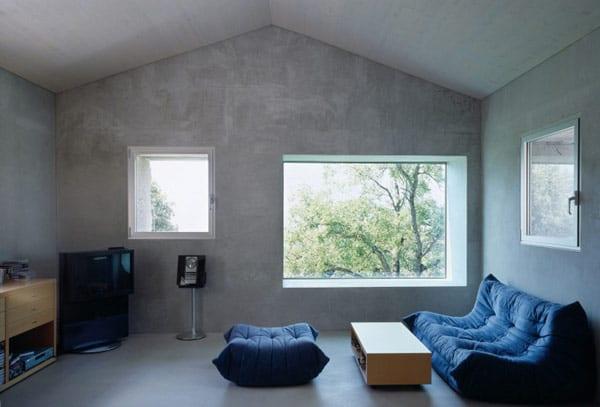 modernes wohnzimmer aus beton-blaue sofa und hocker- holzcouchtisch