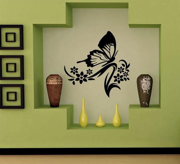 grüne wand dekoration mit holzrahmen und vasen- schwarzes wandtattoo schmetterling