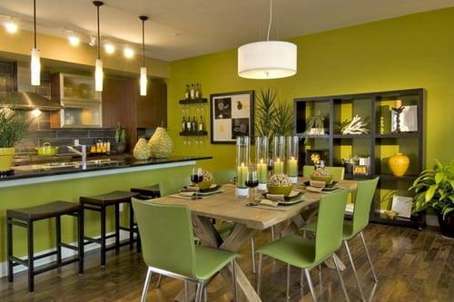wohnzimmer mit grüner wand und massiv hilztisch mit grünen Stühlen- offene küche gestaltung