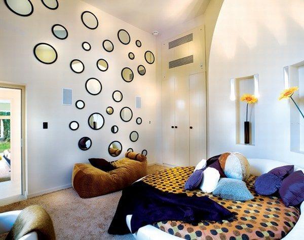 schlafzimmer mit Rundbett- wanddeko mit runden spiegeln mit schwarzen runden spiegelrahmen