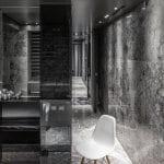 schwarye natursteinwände-wandspiegel gestaltung-weißer stuhl- schwarze wandregale