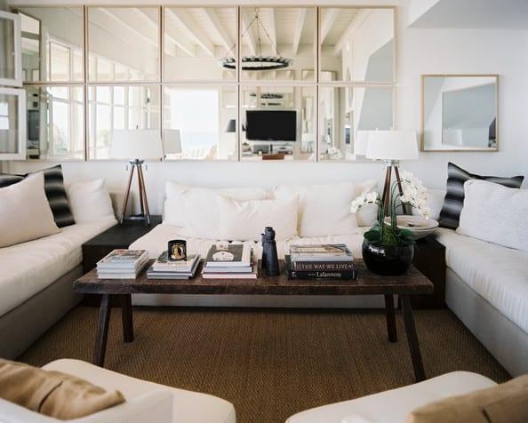 wohnzimmer wandgestaltung mit quadratischen spiegeln und ecksofa in grau und weiß- rattanteppich-holz couchtisch