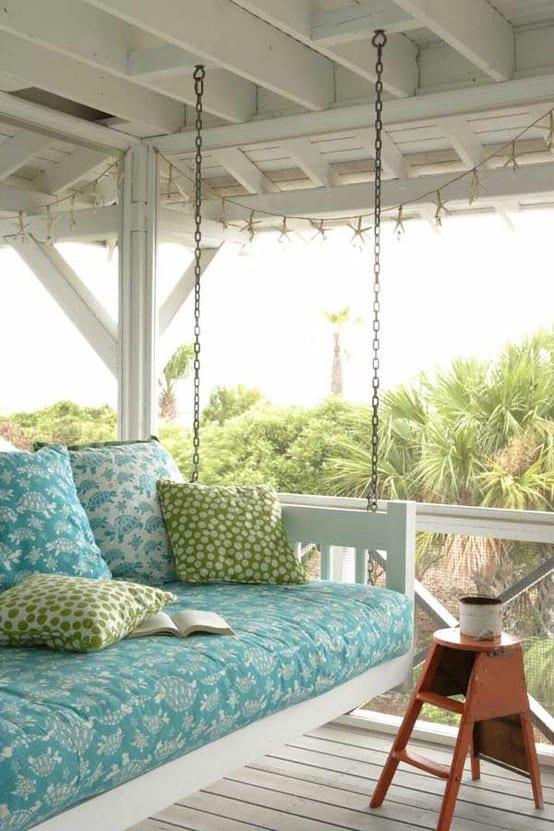 terrassengestaltung in weiß mit schaukel und blauen sitzkissen