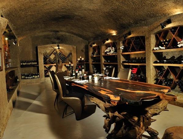massivholztisch mit schwarzen lederstühlen- weinkeller aus stein