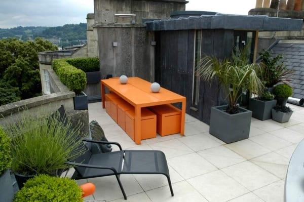 Dachterrasse mit Hecke und Steinfliesen- Esstisch mit hockern in orange