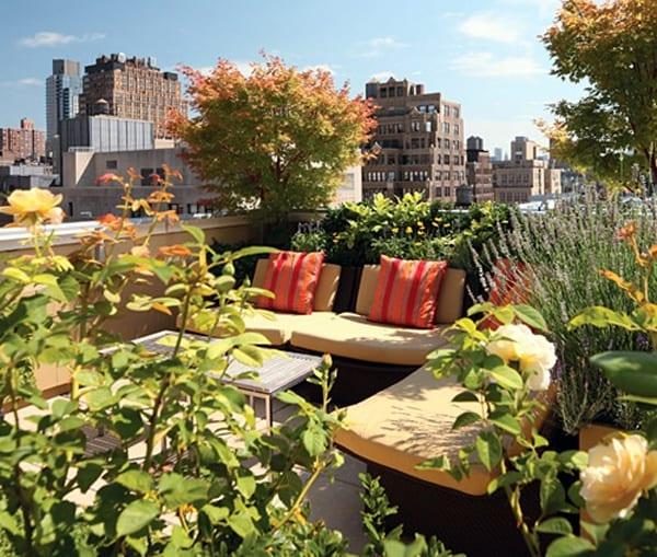 kleiner garten in der Stadt- Gartenmöbel mit gelben Polsterkissen und Kissen mit roten und orangen Streifen