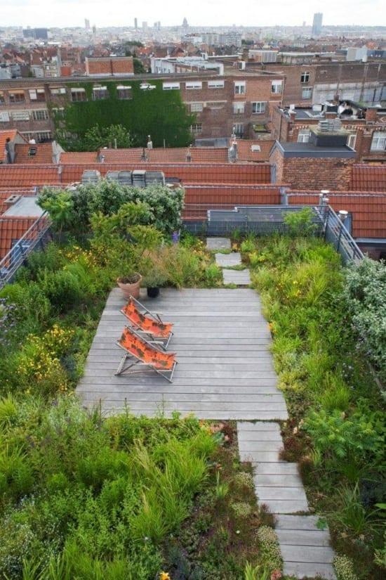 kleiner Garten auf dem Dach mit Holzboden und Sonnenliegen