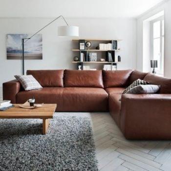 wohnzimmer mit parkettboden weiß und ecksofa leder braun