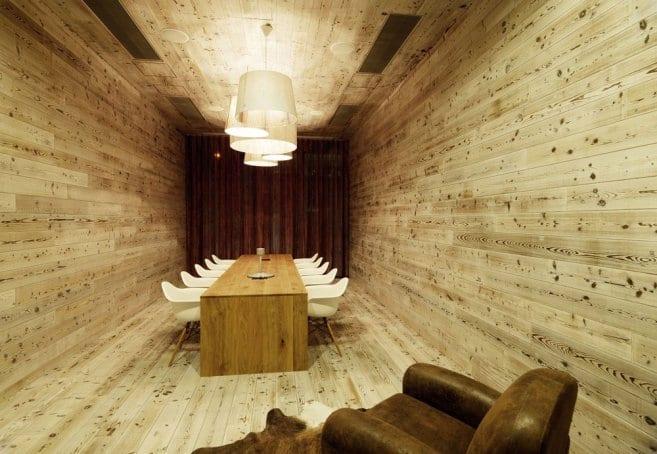Raumgestaltung aus Holz mit weißen deckenlampen und Konferenztisch aus Holz mit weißen stühlen