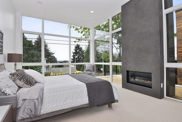 schlafzimmer mit pfostenriegel fassade und grauem kamin