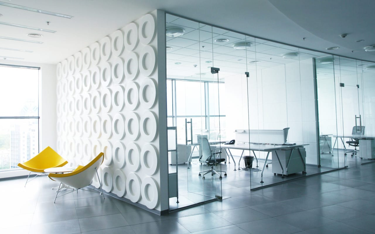 büroräume einrichtungsidee in weiß- wandtextur mit kreisen-designer sessel in gelb-büroräume mit glaswände