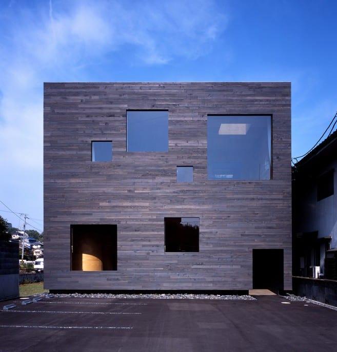 minimalistisches büro office- fassade mit holzverkleidung grau und grosformatigen fensteröffnungen
