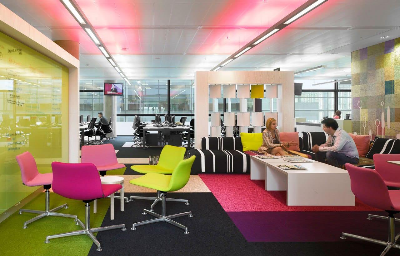 farbige büroausstattung mit Bürostühlen in grün und pink-textilboden in schwarz und violett-grüne glaswand-raumteiler weiß