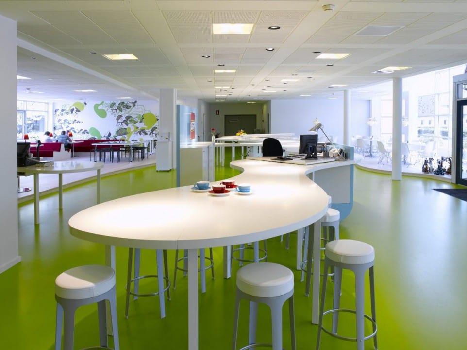 kreativer büroschreibtisch mit weißen hockern- offene büroorganisation