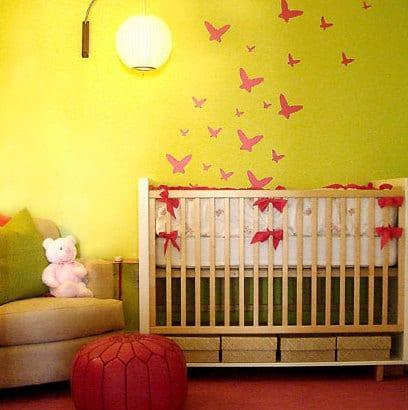 babyzimmer mit gelber Wand und rotem teppich- babybett aus Holz mit dekoration aus roten schleifen