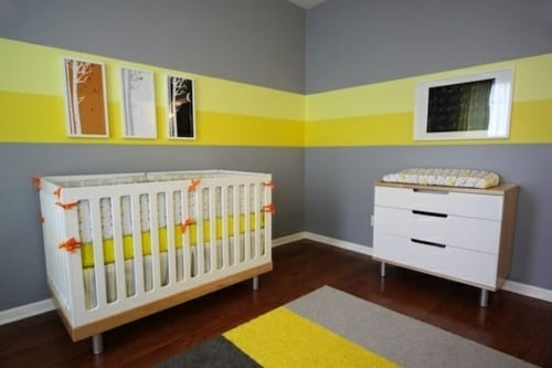 babyzimmer mit Parkett und graue Wände mit gelben Streifen- Teppich mit streifen in gelb und grau- weißes Babybett
