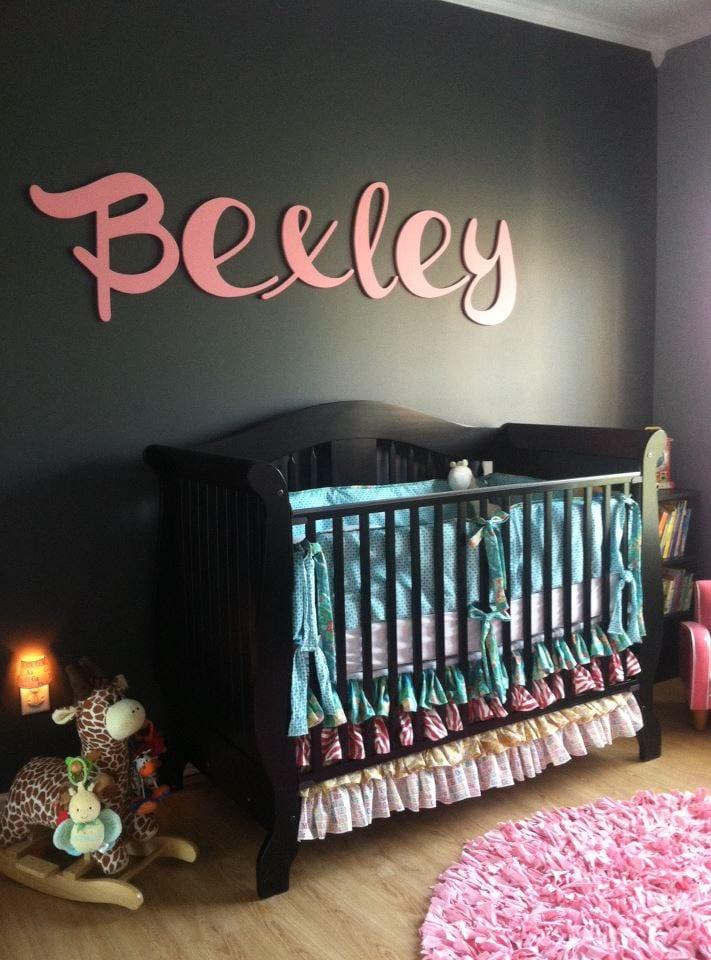 Farbgestaltung babyzimmer-schwarze wand mit rosafarbigem Namenschrift- schwarzes babybett