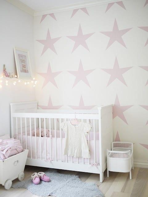 kinderzimmer mit weißen wänden und rosafarbigen Sternen-Wandtatoo- weißes babybett