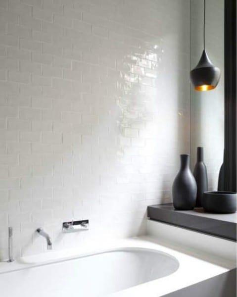 badezimmer mit weißer ziegelwand aus fliesen und schwarzem Fensterbank