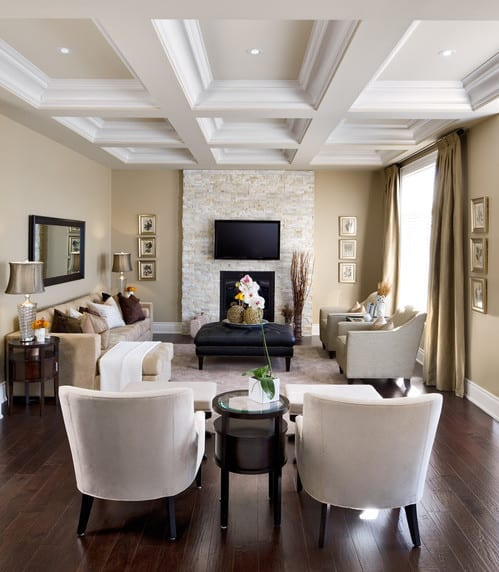 modernes wohnzimmer mit deckengestaltung natursteinwand mit kamin-hockertisch leder schwarz-gardinen und sofa in beige