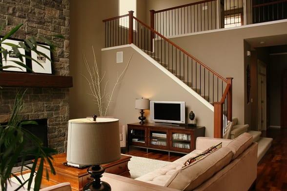 wohnzimmer mit kamin aus naturstein und Holztreppe- kamin dekoration mit holzbalken-wandfarbe taupe