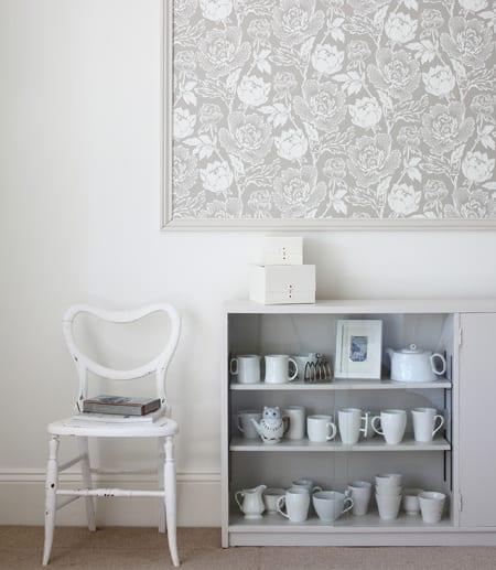 weißer anrichtetisch  und weißer holzstuhl- wangestaltung mit grauem bilderrahmen
