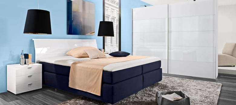 schlafzimmer blau mit bett dunkelblau und weiß- kleiderschrank weiß-laminatboden grau mit teppich grau
