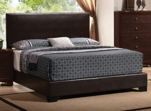 schlafzimmer mit holzmöbeln und bett mit kopfbrett braun.bettwäsche grau