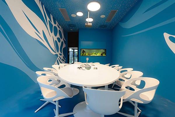 farbgestaltung büroräume mit weißem Konferenztisch und weißen Bürostühlen-wandfarbe  blau
