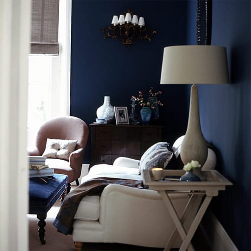 schönes wohnzimmer mit dunkelblauen wänden und weißen polstersesseln-holzkommode-wandleuchte